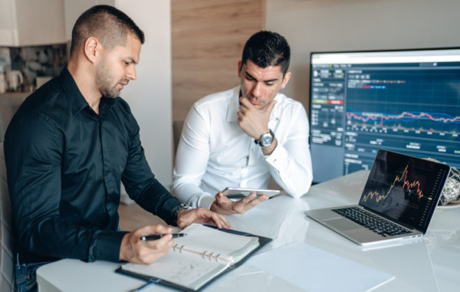 Two men sitting on a white desk, looking through notes and smart devices.